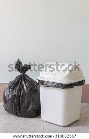 Black garbage bags and dirty white bin - stock photo
