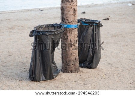 Black garbage bags. Plastic black trash on the beach under the coconut trees. - stock photo