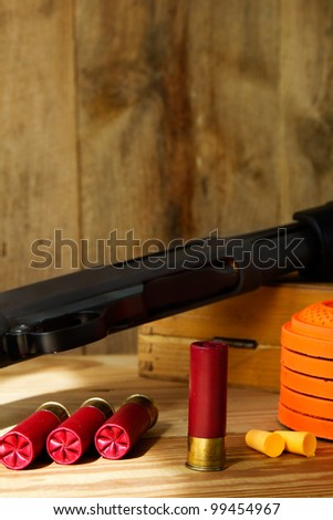 Black 12 gauge pump action shotgun with shells, clay pigeons, and ear plugs sitting next to it. - stock photo