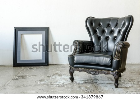 Black genuine leather classical style sofa in vintage room with frame - stock photo