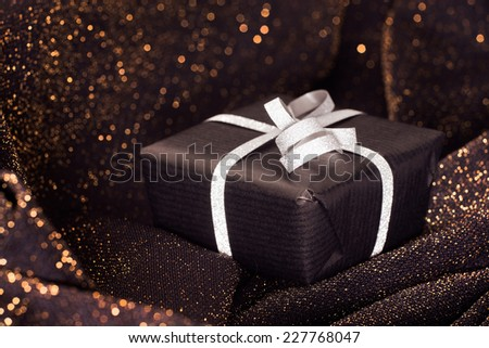Black gift box with silver bow on black shiny background. - stock photo