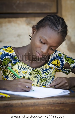 Black Girl Drawing and Writing Letters to Communicate in Africa  - stock photo