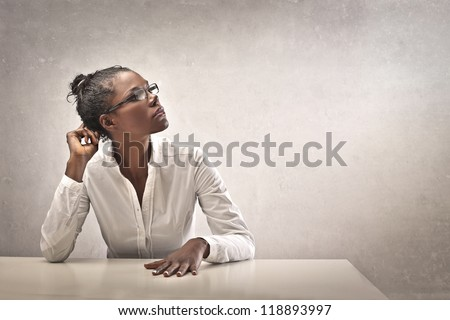 Black girl, leaning on a white desk, thinks - stock photo