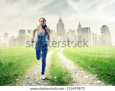 Black girl running in a field near New York - stock photo