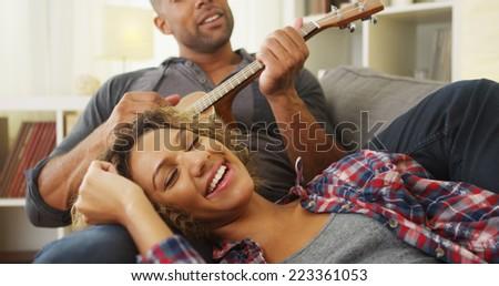 Black girlfriend enjoying being serenaded to by boyfriend - stock photo