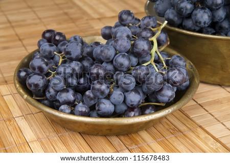 Black grape in copper bowl - stock photo