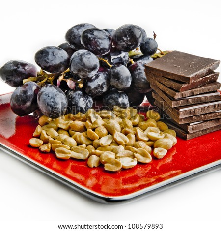 Black grapes, peanuts, dark chocolate: three foods containing resveratrol, which may be good for the heart - stock photo