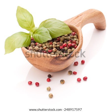 Black, green and pink pepper peppercorn mix in wooden spoon isolated on white background cutout - stock photo
