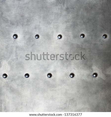 Black grunge metal plate or armour texture with rivets as background - stock photo