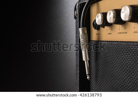 Black guitar amplifier with jack cable on black  background - stock photo
