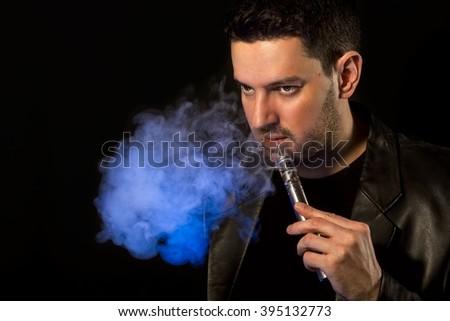 Black haired handsome man vaping e-cirarette custom mod - isolated on black background - stock photo