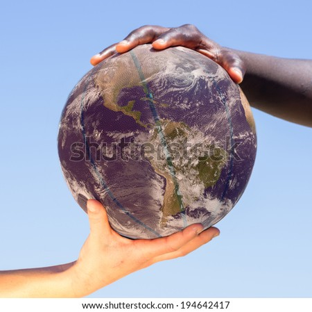 black hand and white hand holding a ball,concept of peace and humanity,earth photo by NASA - stock photo