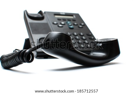 Black handset and a phone - stock photo