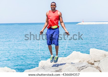 Black handsome man jumping rope with sea view in background - Male runner doing exercise and preparing for morning workout outdoor - Healthy lifestyle concept - Soft focus on him with warm filter - stock photo