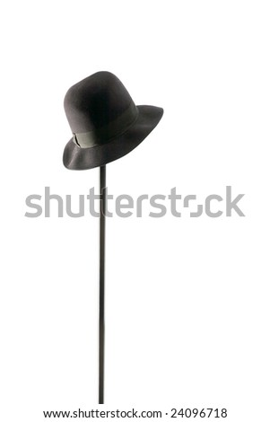 black hat hangs on  metal hanger, isolated - stock photo