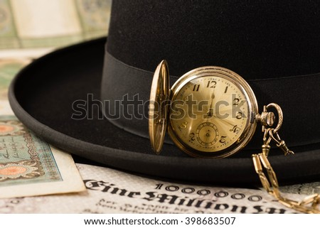 Black hat with a pocket watch on lots of money - stock photo