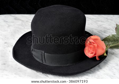 Black hat with red roses on a marble table, fashion - stock photo