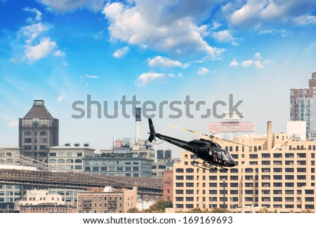 Black helicopter flying over New York City. - stock photo
