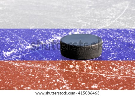 Black hockey puck on ice rink with Russian flag. - stock photo