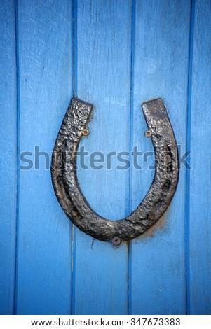 black horseshoe on a blue wooden door - stock photo