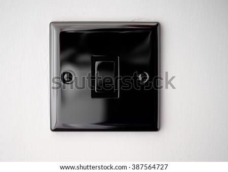 Black house hold light switch on a white wall - stock photo