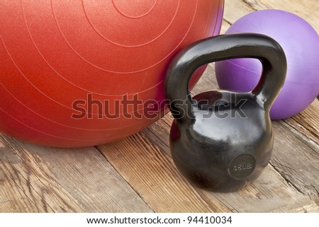 black iron kettlebell, Swiss and medicine exercise balls on wooden deck - fitness concept - stock photo