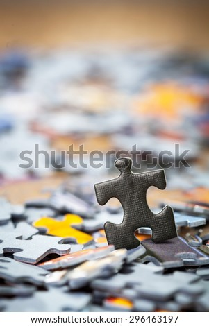 Black jigsaw puzzle piece on heap of color puzzle pieces. Shallow depth of field - stock photo