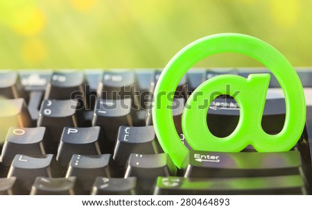 Black keyboard with green sign at and sunlights. Ecology concept - stock photo