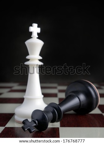 Black King lying on chessboard by the winning white King - stock photo