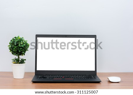 Black laptop on wooden table on white wall - stock photo