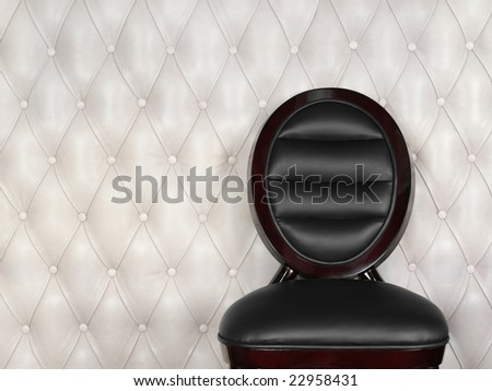 Black leather chair near white wall - stock photo