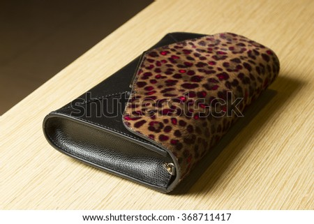 Black leather clutch with an insert made of fur leopard. - stock photo