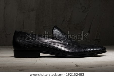 Black leather mens shoe on a wooden surface - stock photo