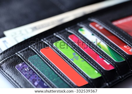 Black leather wallet with colourful credit cards and money, close up - stock photo