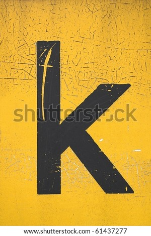 Black letter k on yellow grungy background - stock photo