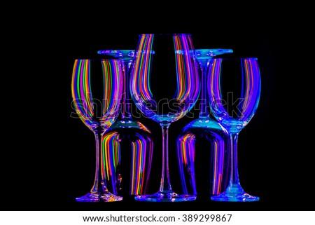 Black light and wine glasses rainbow. - stock photo