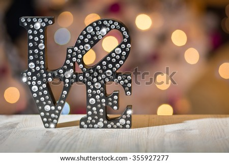 Black love sign with crystal sparkles on blurred lights background - stock photo