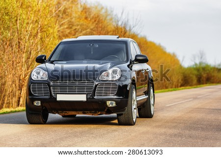 Black luxury car at byroad in autumn time - stock photo