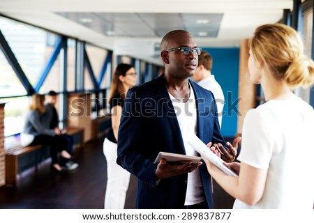 Black male executive standing and talking to white female colleague holding notepads - stock photo