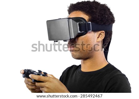 Black male wearing a virtual reality headset and holding a controller on white background.  He is wearing the device as goggles over his eyes.  - stock photo