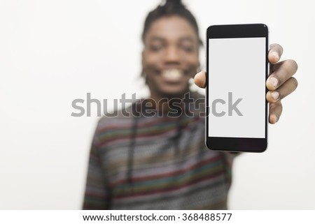 black man holding out hand to show blank white screen of cell phone with clipping path concept. Model is smiling and dressed in casual clothes.  - stock photo