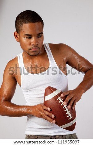 Black man in an undershirt holding an American football with sweat on his arms and chest, ready to throw the football. - stock photo