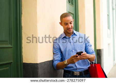 Black man in Casco Antiguo - Panama City with shopping bags. The guy leans on a wall and types message with his phone on social network.  - stock photo