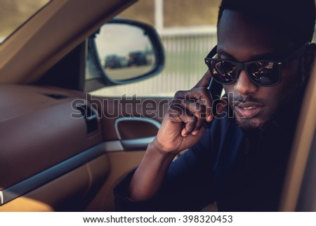 Black man in sunglasses talking by smartphone in the car. - stock photo