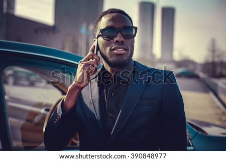 Black man in sunglasses talking by smartphone near the car. - stock photo