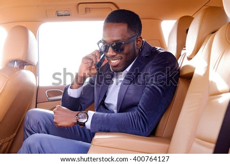 Black man in sunglasses with smartphone in the car. - stock photo
