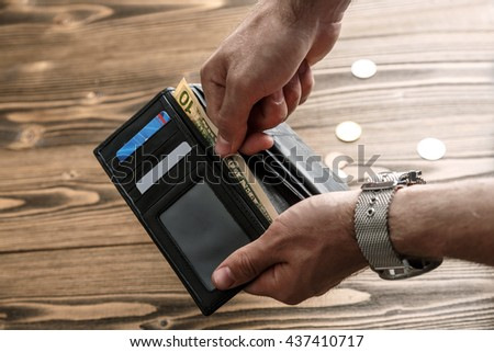 Black man's wallet in man hands pulling out a banknote over dark wooden background - stock photo