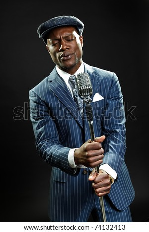 Black man with blue striped suit and cap singing. Jazz musician. Night club. Cotton club. New Orleans. - stock photo