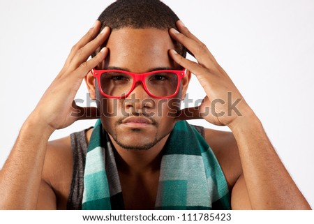 Black man with pink eye glasses with his hands up to his head, eye contact with the camera and a serious expression - stock photo