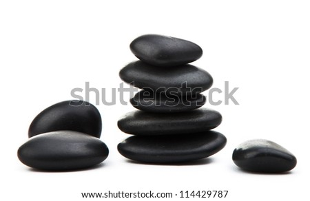 Black massage stones stacked, isolated on white - stock photo